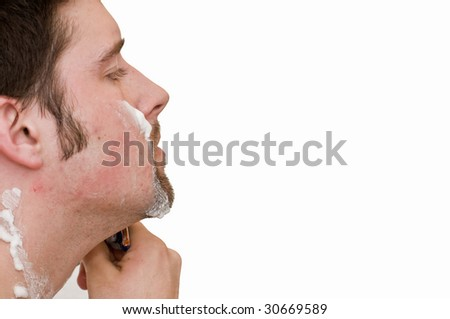 White male shaving his face