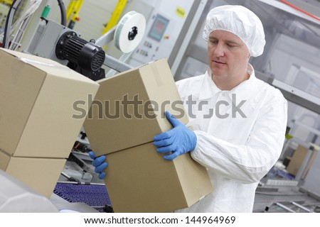 White male  worker working on packing line in factory - stock photo