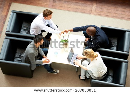 White man and black man shaking hands during a work meeting - stock photo