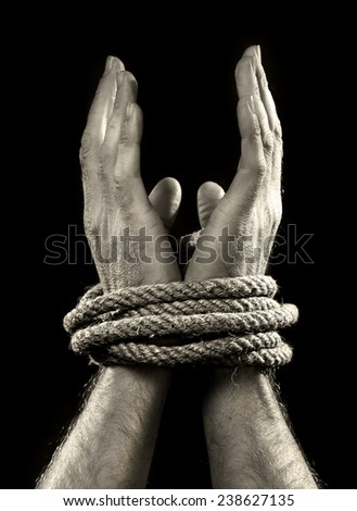 white man hands wrapped with rope around wrists in captivity , victim abused , slave of work , respect for human rights and exploitation concept isolated on black background - stock photo