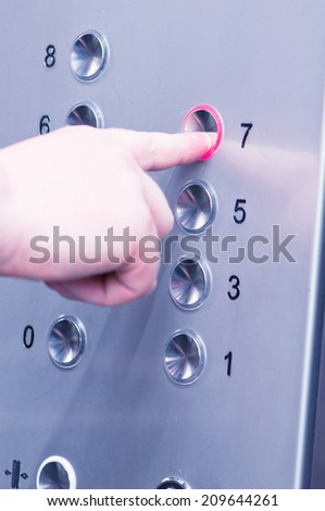 white man pushing buttons on an elevator - stock photo