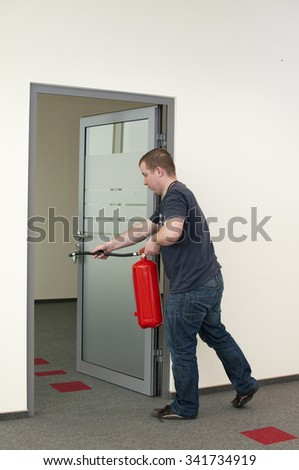 white man running with a fire extinguisher - stock photo