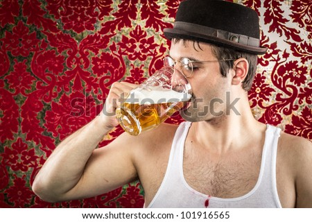 White man with glasses, hat, wife beater, brown hair chugging light beer alone in retro red and gold background bar - stock photo
