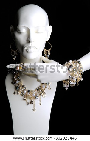 White Mannequin with Jewelry Rings Bracelets Necklaces and Earrings - stock photo