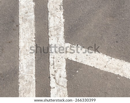 white markings on the old dirty gray asphalt - stock photo