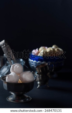 White marshmallows on glass jar on black background