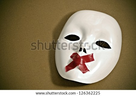 white mask with red tape strips forming a cross in its mouth on a brown background - stock photo