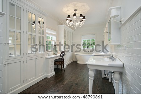 White master bath with dark wood floors - stock photo