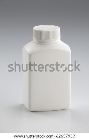 White medicine bottle closed on plain background - stock photo