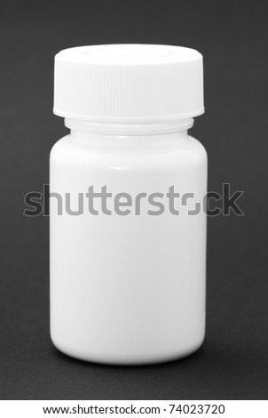White medicine bottle on black background - stock photo