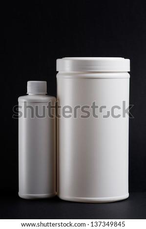 White medicine bottles on black background - stock photo