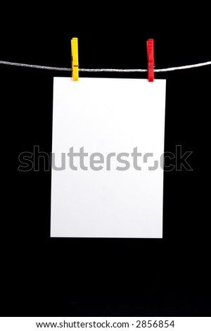 White memo hanging on yellow and red clothespin on clothesline - isolated on black background
