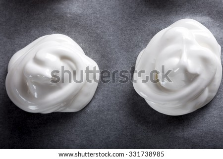 White meringues on baking paper on a baking tray - stock photo
