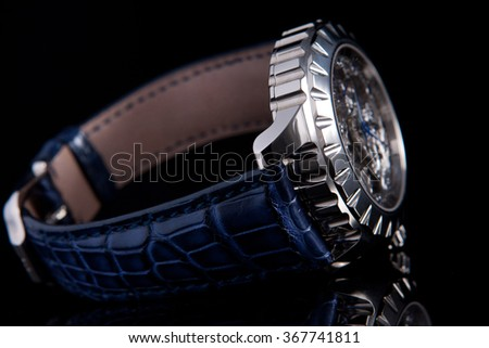 White metal case skeleton watches with blue hands and blue sapphires on blue alligator leather strap side view - stock photo