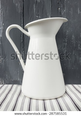 White metal milk pitcher on wood. - stock photo