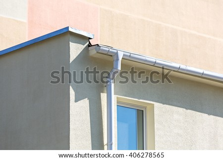white metallic gutter and drainpipe on plaster wall of building - stock photo