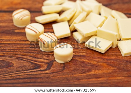 White milk chocolate truffles candies pralines on brown wooden background, close up