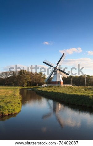 White mill standing at a canal at a tranquil evening. - stock photo