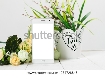 White mobile phone with a blank screen in the flower arrangement on the table - stock photo