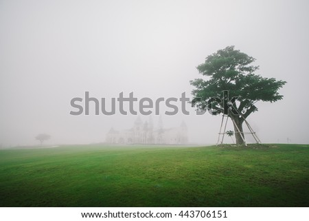 white modern castle with fog - stock photo