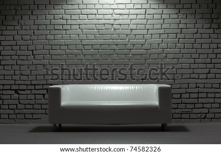 white modern leather sofa and brick background - stock photo