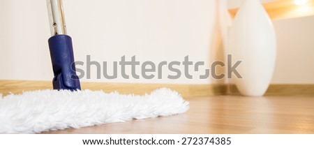 White mop cleaning wooden floor from dust in modern interior - stock photo