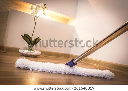 White mop cleaning wooden floor in house - stock photo