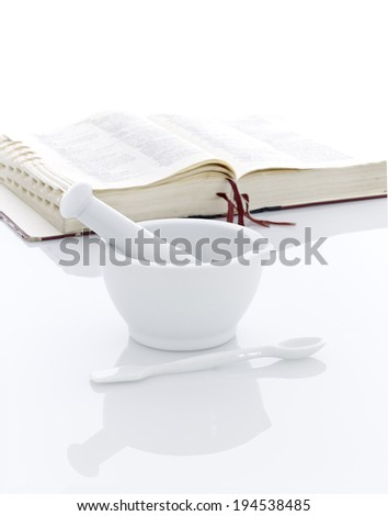 white mortar on white table top with book - stock photo