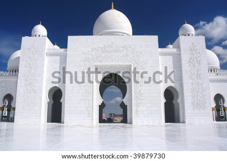 white mosque with cloudy blue sky in Abu Dhabi - stock photo