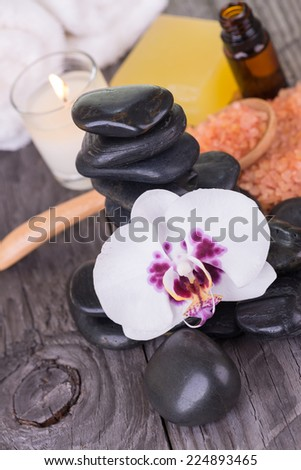 White Moth orchid, black stones, essential oil and bath salt close up - stock photo