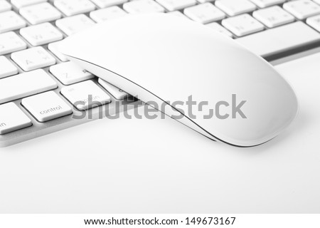 White mouse over keyboard on white background
