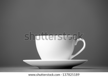 White mug and saucer on a gray background. - stock photo