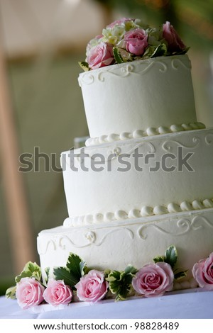 white multi level wedding cake with pink flower decorations - stock photo