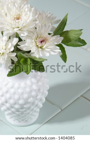 White mums in a hobnail milk glass vase. - stock photo
