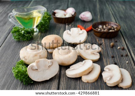 White mushrooms champignons, old wooden table, rustic style, selective focus