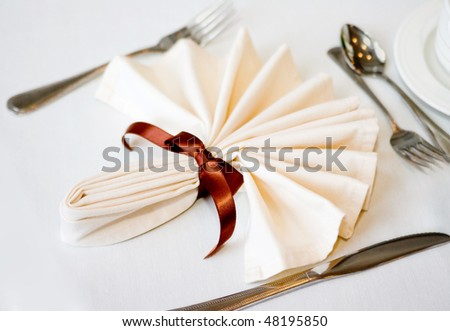 white napkin and place setting with brown ribbon and flatware on a white tablecloth - stock photo
