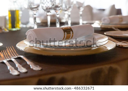 White napkin held by golden clutch lie on a set of golden plates