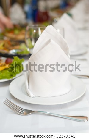 white napkins folded as triangles on plates, in perspective, on laid banquet table, shallow DOF - stock photo
