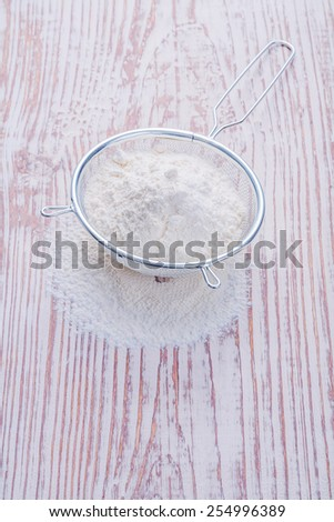 white natural flour  in sieve on vintage wooden desk food and drink concept  - stock photo