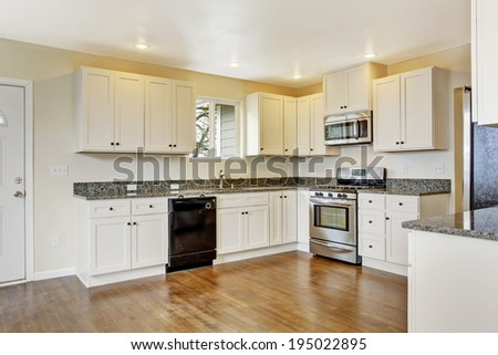 White new small simple classic American kitchen interior. Shiny hardwood floors.
