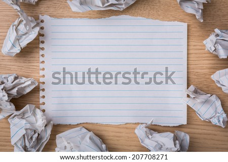 White note book paper with  pencil and crumpled paper  on a wooden desk - stock photo
