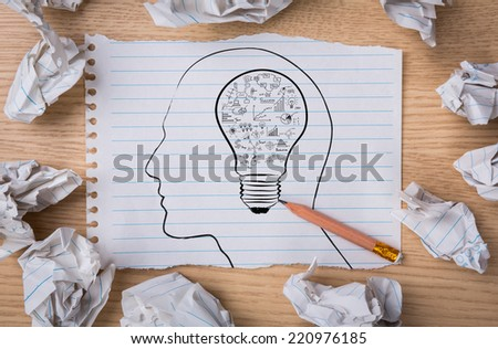 White note book paper with  pencil draw  light bulb inside a head and crumpled paper  on a wooden desk - stock photo