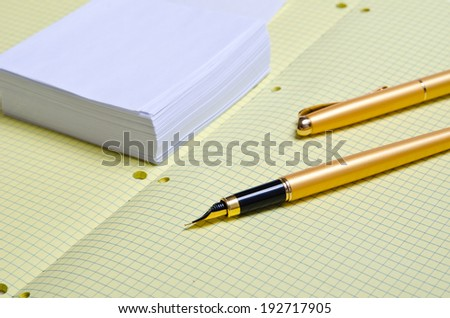 white note paper and golden pen, school notebook with pen, crumpled crumpled sheets with entries