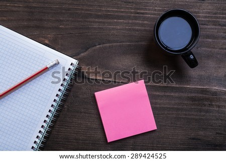 White notepad pencil reminder note and cup of black coffee on pine wooden board office concept  - stock photo