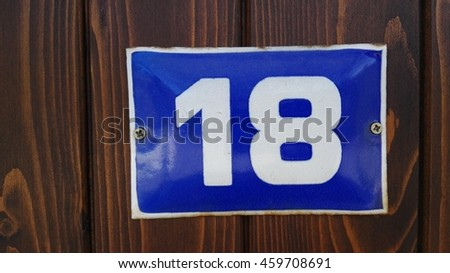 white number 18 on a blue plate mounted on a wooden door - stock photo