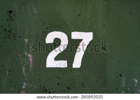 White number 27 on old metal panel painted in green  - stock photo