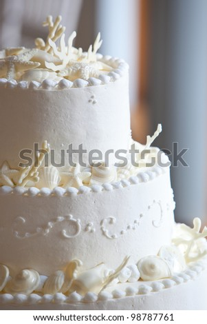 white ocean themed wedding cake with miniature seashell design and details - stock photo