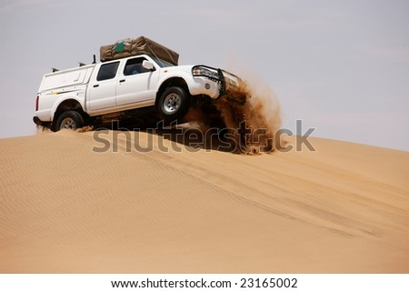 White off-road car fetching a dune, side view