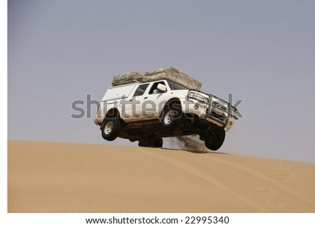 White off-road car on the top of the sand dune - stock photo