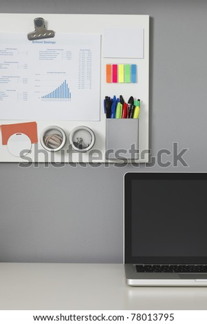 White office desk, laptop computer and a white magnetic board on a gray wall - stock photo